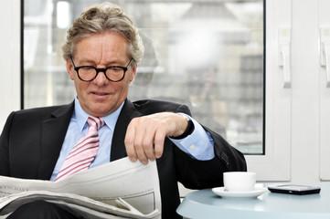 Manager mit Zeitung und Kaffee