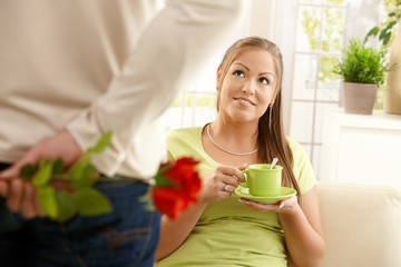 Man bringing flower to woman