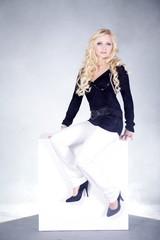 Blonde Frau sitzend auf Würfel
