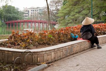 Asiatische Person vor der Brücke der Aufgehenden Sonne in Hanoi