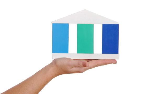 Hand mit Haus aus Bauklötzern