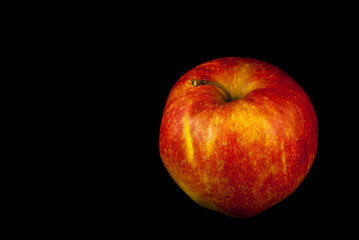 Single red apple on black background
