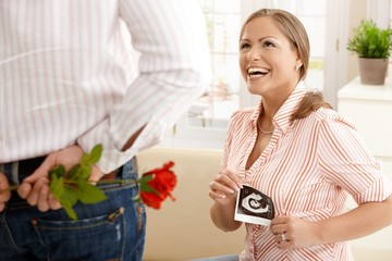 Laughing pregnant woman getting flowers