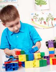 Child with  construction set in play room.
