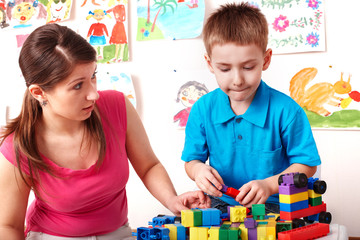 Child and teacher with construction set in play room.
