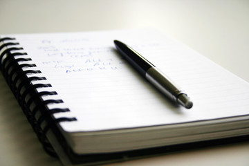 A black pen and writed notebook.