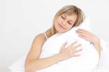 Relaxed woman hugging her cushion sitting on her bed