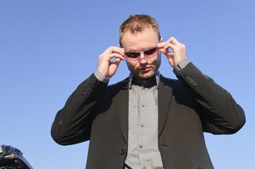 Junger Mann im Anzug zieht seine Sonnenbrille ab