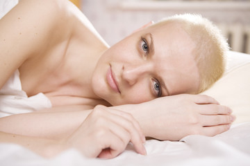 blond serious woman lying on bed