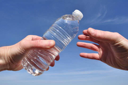 Hand Offering a Bottle of Water