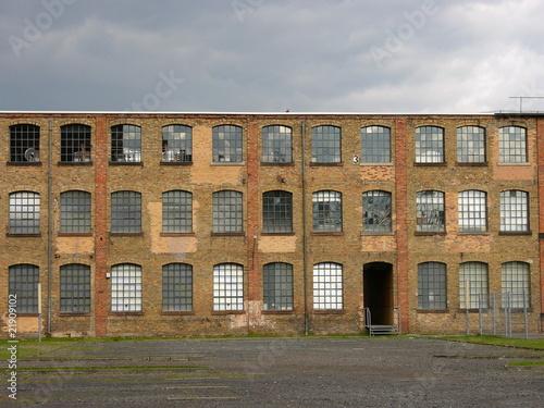 Fassade der alten Heyne Fabrik mit grauen Regenwolken am Himmel in ...