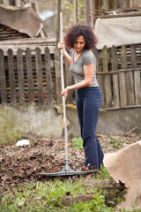 Redhead woman using a rake for cleaning