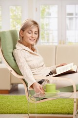 Woman with coffee mug and book at home