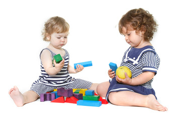 two cute toddler girls playing over white