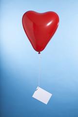 roter luftballon in herzform mit leerer grußkarte