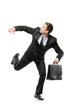An afraid businessman running away isolated on white background