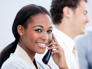 Smiling Afro-American businesswoman talking on phone