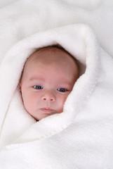 bébé emmitouflé dans un essuie blanc