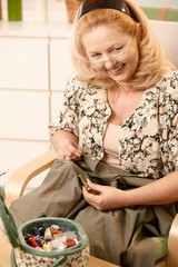 Smiling senior woman with sewing kit