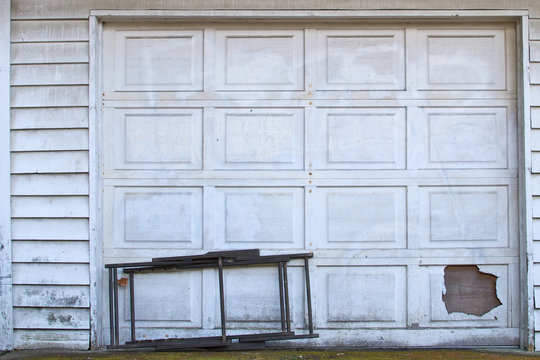 Aging white garage door with discarded lawn chair
