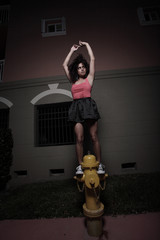 Woman posing on a fire hydrant at night