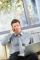 Businessman on call with laptop on sofa