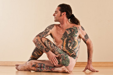 yoga master rotates into a spinal twist pose