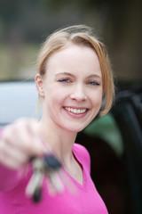 frau mit schlüssel vor dem auto