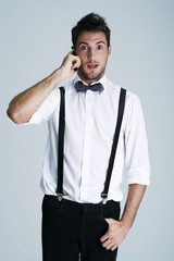 Young man in suspenders on the phone