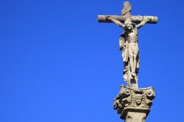 Jesus Christus am Kreuz, Steinfigur vor blauem Himmel