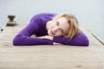 junge frau entspannt auf einem steg am see
