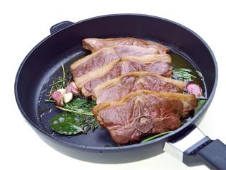 saddle of lamb, garlic & herbs roasting in a pan