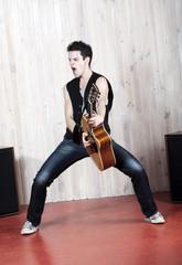 jeune homme acharnement sur sa guitare
