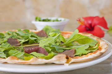 Meat pizza on a thin base with green salad topping
