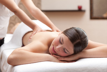 Woman enjoying a back massage in a spa setting