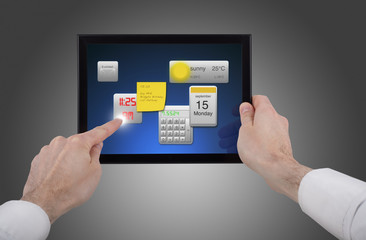male hand holding a touchpad pc, using different programmes