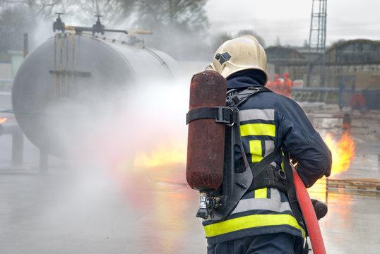 Firefighter extinguishing tank fire