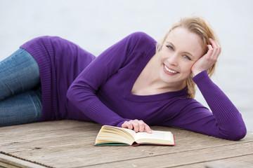 junge frau liegt am see und liest ein buch