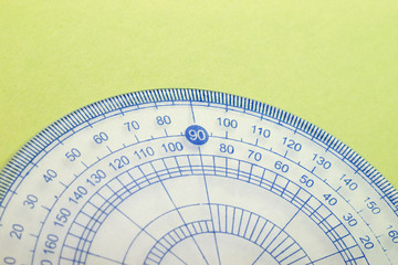 Closeup of transparent blue protractor on green paper texture