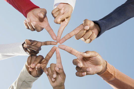 Multi-ethnic friends pointing fingers in circle