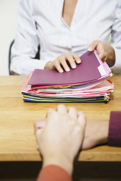 Mixed Race businesswoman with stack of folders