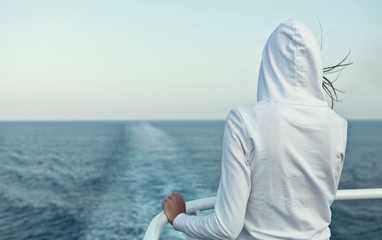 Young woman looking at the ocean from a fast going liner.