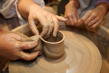 Hands of master creating pot on potter's wheel.