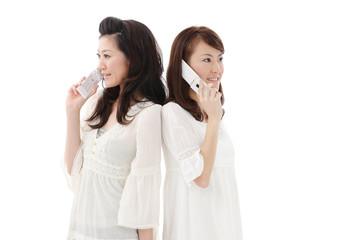 携帯電話で話す女性二人