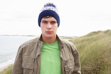 Teenage Boy Standing In Sand Dunes Wearing Woolly Hat