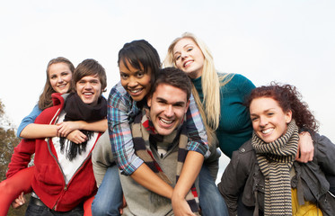 Group Of Teenage Friends Having Piggyback Rides In Autumn Landsc
