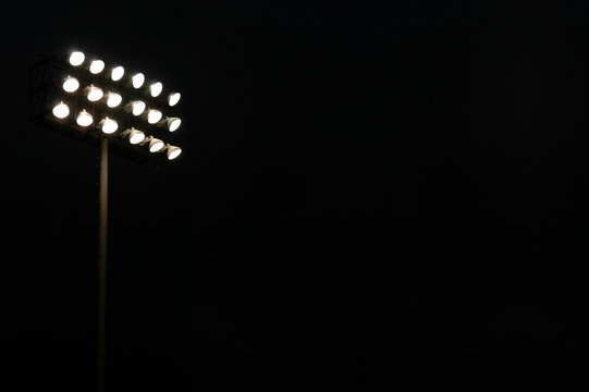 Stadium lights on a sports field at night with copy space