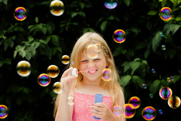 Small girl blowing soap bubbles