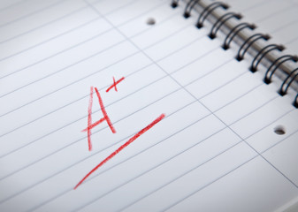 A+ grade in red letters  written in a spiral pad