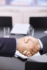 Businessmen shaking hands over table